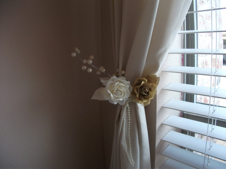 These are the homemade tiebacks my daughter made for her curtains. She already had metal holdbacks and all she did was wrap flowers and other floral pieces around the hold backs, but you could get away with not having any metal holdbacks and just tie a floral band around the curtain and pin the floral tieback to the wall hidden underneath so that you cannot see the pin. Another idea is to add tool to the flowers by pushing the flowers into the tool, and continue making your arrangement this…