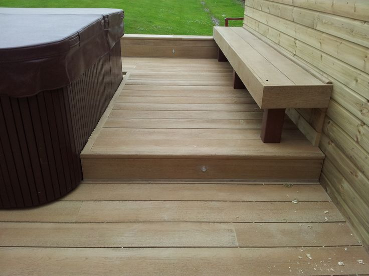 Millboard composite decking set around a hot tube raised up to make it easier to get in and out supplied and fitted by the Original Decking co ltd