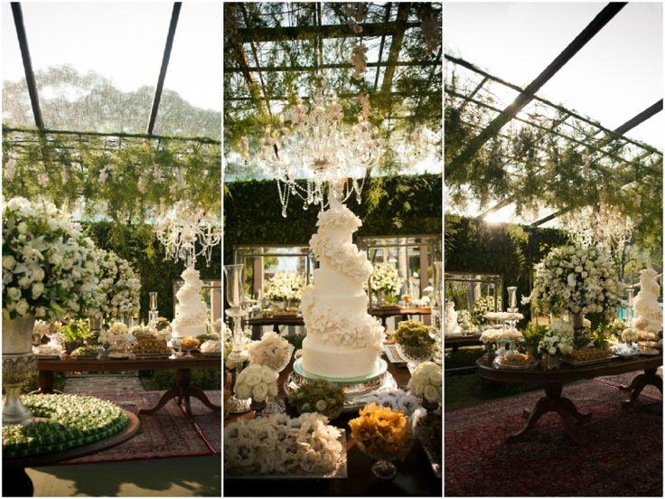 Bolo tradicional de cinco andares foi iluminado por lustre de cristal e pergolado de folhagens