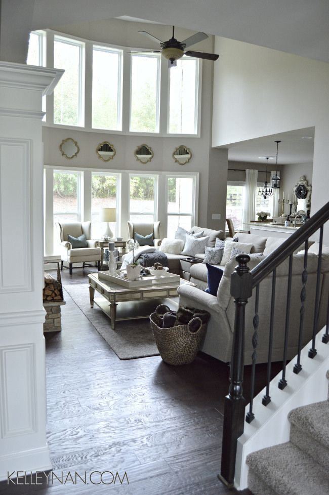 neutral living room | two story living room | neutral decor living room | living room ideas | la-z-boy sectional | zgallerie palais coffee table | quatrefoli mirrors between windows | bow of windows | pottery barn thatcher wingback | navy fall decor | gray fall decor | neutral living room inspiration