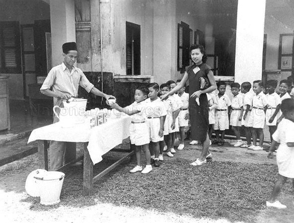 A MAN GIVING OUT FREE SKIMMED MILK TO STUDENTS DURING RECESS …