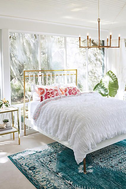 Incredible interior for the bedroom. Super bright and sunny, white paneling on the ceiling, a deep teal rug, large-leafed potted plant, brass and glass accents.