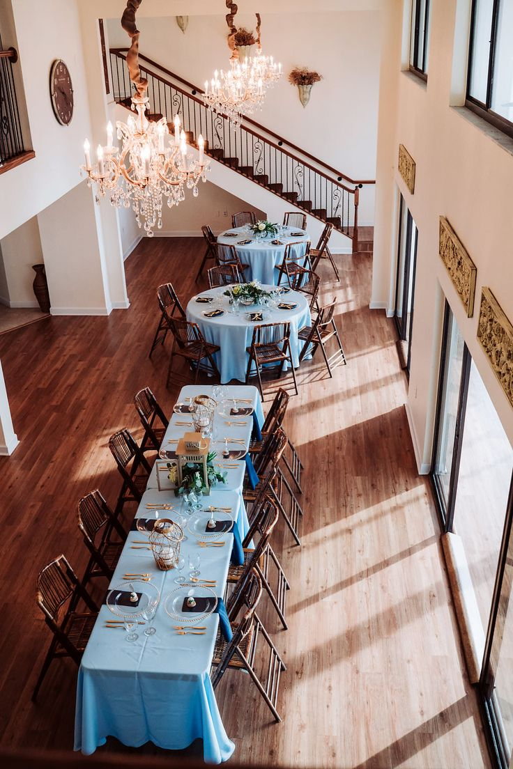 Coastal Glam Wedding Reception Long Feasting Table with Blue Linens, Low Natural Greenery and Hurricane Lantern Centerpiece, Bamboo Folding Chairs, and Gold Chargers and Flatware | Tampa Bay Waterfront Wedding Venue Beso Del Sol Resort | Wedding Rentals Coast to Coast Event Rentals
