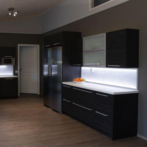 Hirsitalon kalustuksesta haluttiin moderni vaikka talon rakennusmateriaali onkin perinteinen. Talon sydän on iso nykyaikainen tupa, missä keittiö yhdistyy oleskelutilaan.  Tumma keittiö sopi hyvin tilaan koska väritys oli muuten vaalea ja isot ikkunat antavat valoa. Keittiön ovimallina on kaunis eläväpintainen kalvo-ovi vaakakuviolla. Korkeassa tilassa matala yläkaapisto on keveä.