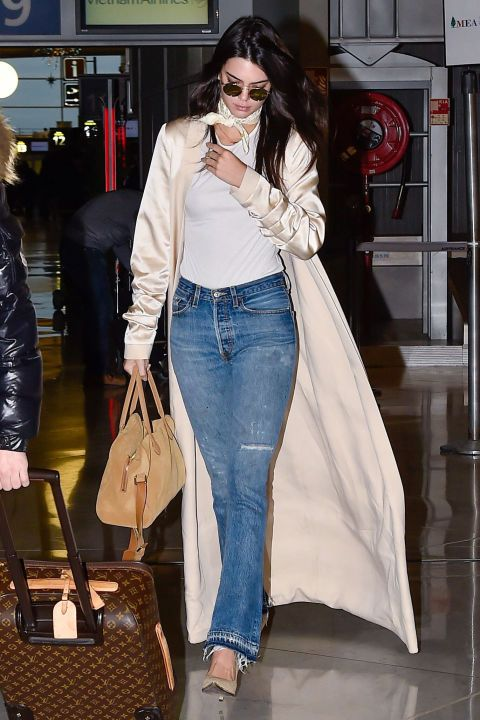 Once again, Jenner jet-sets in style as she arrives at the Paris airport wearing an August Getty Atelier jacket over a simple tee and Re/Done jeans, paired with a chic neck scarf.