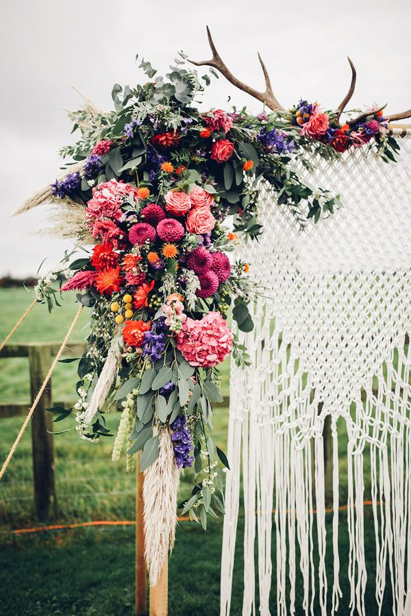 A burst of vibrant flowers on even a corner of your wedding backdrop gives a pop of color unrivaled by anything else. These warm tones match perfectly the coziness of the hanging knit and the rustic antlers. It's a boho look that has achieved the balance between charmingly wild and very polished.