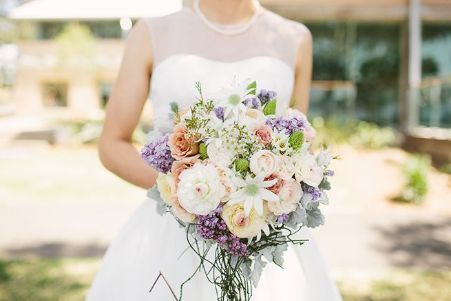 Bridal bouquet in green, light corals and purples with roses, ranunculus, flannel flower, chincherinchee, dusty miler and vine | Blooms by Bethan