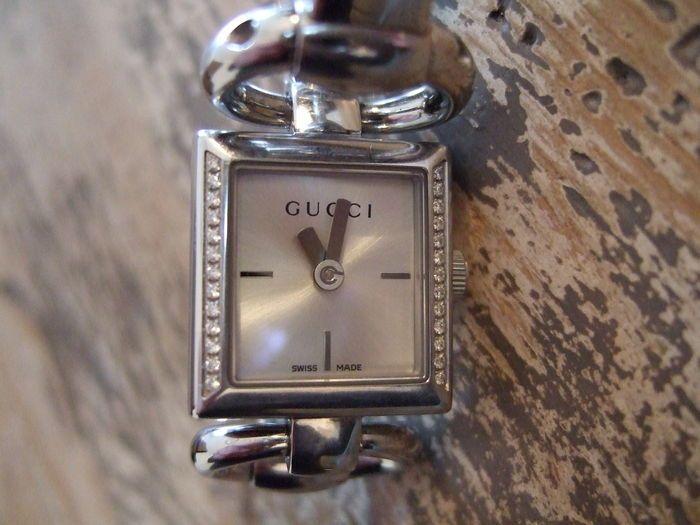 Gucci - dames polshorloge met diamanten  GUCCI-dames horloge met diamantenRoestvrij staal Quartz met doos en papieren.Vervaardigd: ZwitserlandMateriaal: roestvrij staal met diamond bezelMovement: Quartz batterijKroon: OndertekendCase diameter: 18cm vierkant met uitzondering van kroon: hoogte: 5mmDial: SilverBandje: roestvrij staalLengte riem: de grootte van de pols tot 150mm met 15mm extra koppelingenBand breedte: 5mmGesp: ondertekendTotaal gewicht: 37gType display: AnaloogMet doos en…