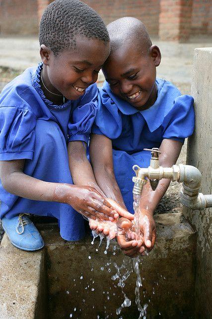 Rwanda ~ outside a school...bittersweet that water is what brings such joy
