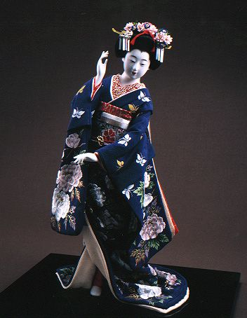 A pretty maiko doll in a dark blue hikizuri decorated with butterflies and peonies.