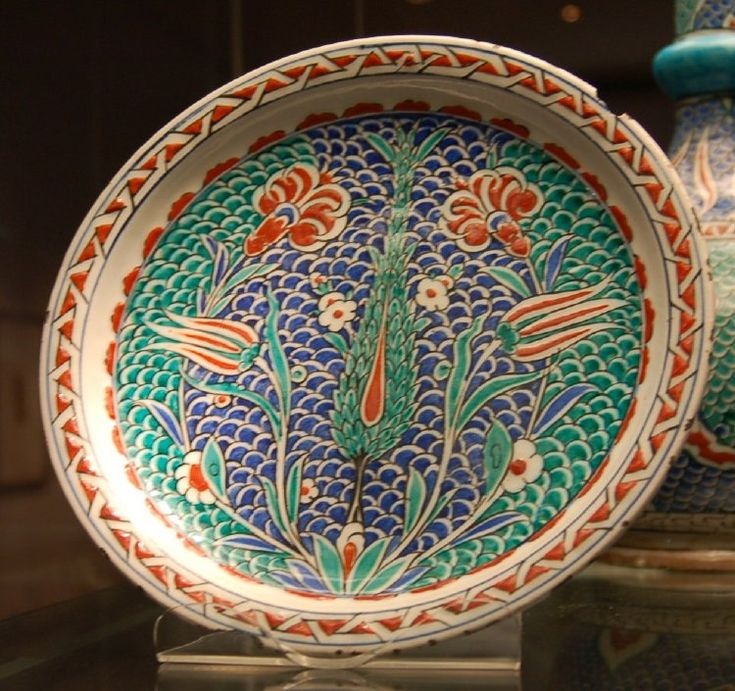 Dish. Cypresses and a vertically symmetrical composition of florist's flowers on a scale ground.Rim has cable band.Cavetto lappets. Made of black, cobalt, turquoise, red (bole) painted and glazed ceramic, pottery.