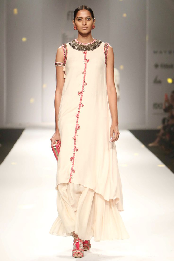 Featuring an egg shell cut sleeved long kurta in rayon moss base with cutdana, ghunghroo and kantha work on neckline and asymmetrical hem. It has tassel detailing down the front. The details include cut out with sea shell tassels dori closure at the back. It comes along with a matching half and half satin and gauge gathered skirt. Fabric: Rayon moss, satin, gauge  Care Instructions: Dry clean only.