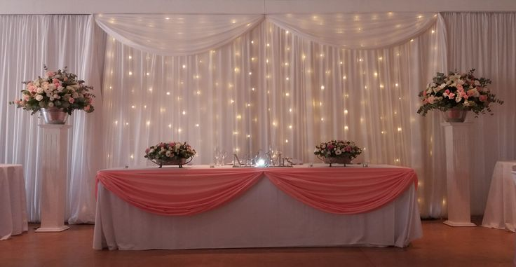 Pretty bridal backdrop with fairy lights and table swags. www.eventsdraping.co.za