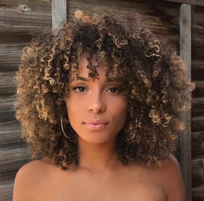 Healthy and natural curls with blond highlights, her hair looks mosturized and lovely.