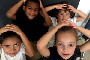 Four young children look up at the camera while their hands are on their heads.