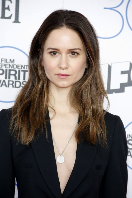 Katherine Waterston Long Hairstyle for Spring  How To Style: Apply a product to create some grit and texture on wet hair. Power dry the hair. Wrap sections of hair from the midshaft to the ends very loosely around a large curling wand in random directions, leaving the hair close to the roots straight. Stretch the sections for a bit as they cool to loosen the wave. Scrunch and rough up the hair with fingers and a product for texture to make the waves look more organic.
