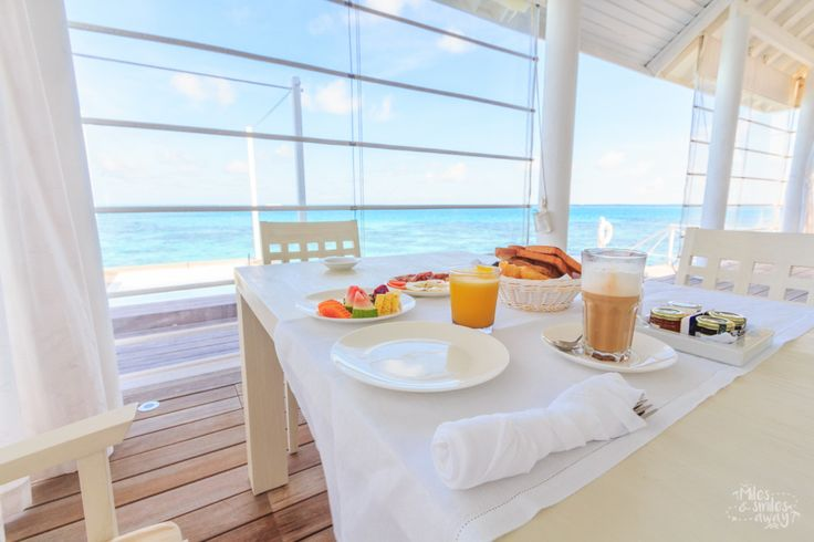 Delicious breakfast with an amazing view from an all white villa at Diamonds Thudufushi resort in Maldives.