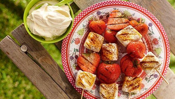 Marshmallow-Aardbeienspies van de barbecue, bestrooid met cacaopoeder en geserveerd met slagroom
