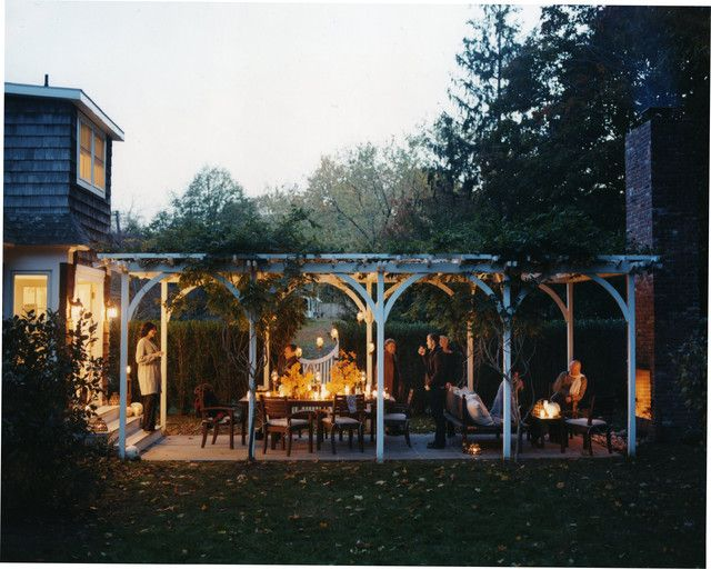 Large white pergola on patio just off the back of the house with fireplace at farthest end of pergola. Nice party room.