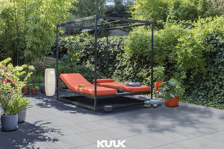 Het zonnetje begint door te komen en het is tijd om bij te bruinen. Hier zien we een liggende lounge set die staat op de Forest Concrete Grey tegels. De gladde tegels zorgen voor een luxe en tropische uitstraling in samenstelling met de zon. #tuininspiratie #tuin #kuuk #zon