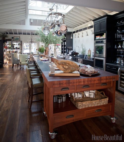 Love the enormous wooden Island with bar stools, giant sky light, White