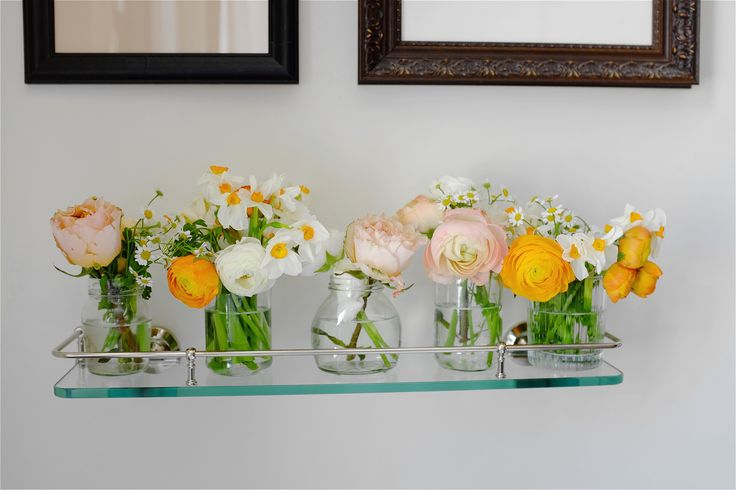 Jam jar wedding table arrangements in an Easter palette with daisies, daffodils, garden roses, ranunculus