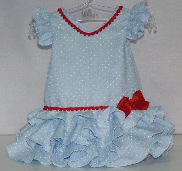 Traje de gitana flamenca para bebe niña de popelín celeste con lunares blancos, adornado con madroños y lazo rojo a juego. Abierto por la espalda con botones para más comodidad. Braguita a juego. Solo 48€