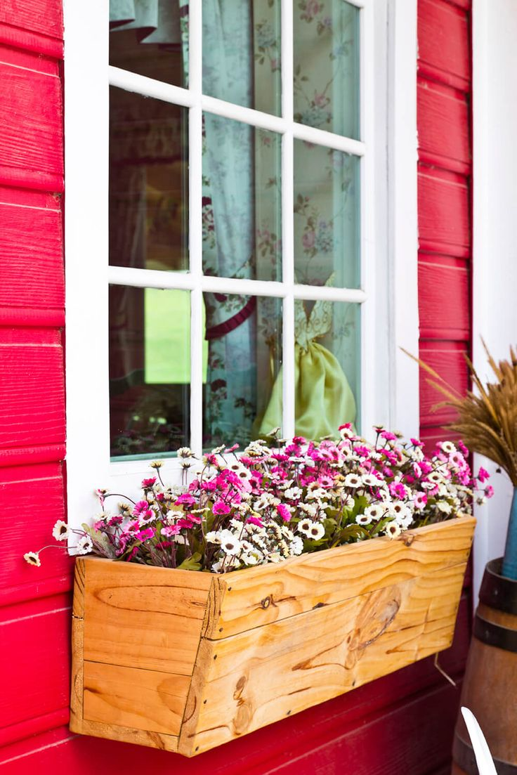 An unfinished wooden window box on the side of a barn-red building is filled with pink and white daisies for a rustic, classically country style.