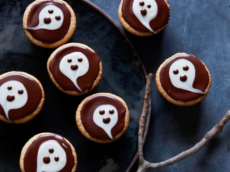 "Ghostly Cupcakes : Spook your guests with these ""boo-tiful"" cupcakes topped with chocolate ghosts. For the design, you simply glaze plain cupcakes with melted dark and white chocolate. You can use the cake recipe here, or try the technique on your favorite red velvet, peanut butter or chocolate cupcakes instead."