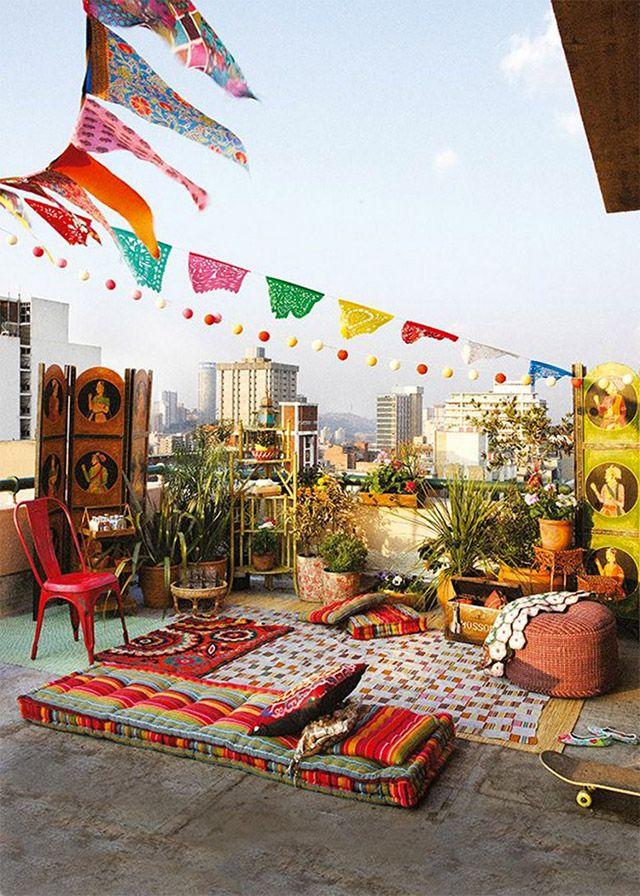 Terraza con cojines y textiles estilo hindú en tonos rojos y decoración aérea multicolor