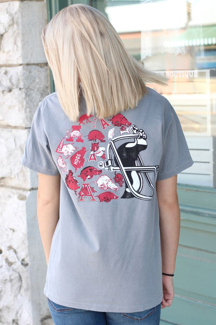 "Short sleeve comfort color brand tee in grey with a football helmet graphic on the back featuring all the past and present Arkansas Razorback Hog logos. Pocket on front left chest with ""Arkansas 'A'"""