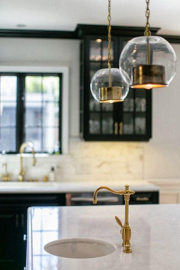 black kitchen cabinets, white counters, brass/gold faucet and cabinet pulls