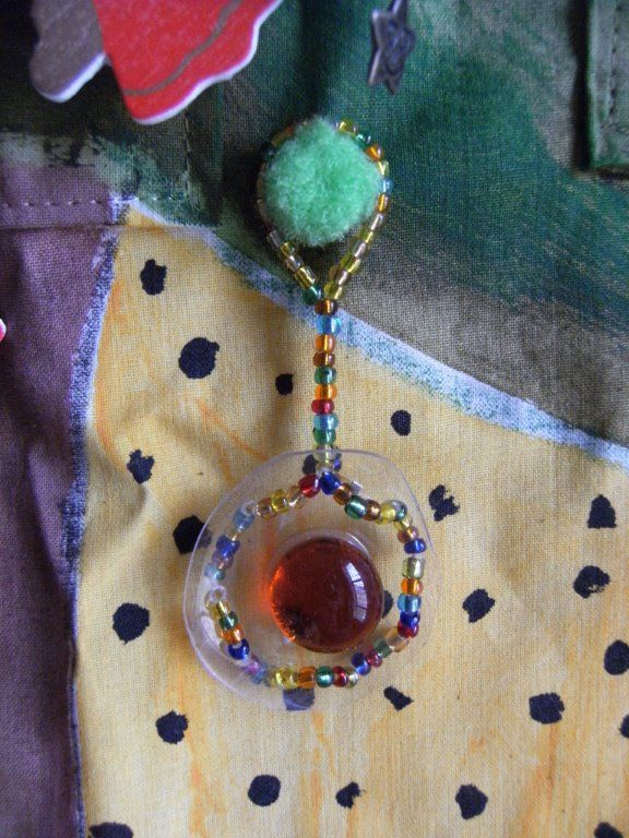 Beaded Xmas decoration - the base in a piece of ironed recycled plastic bottle.
