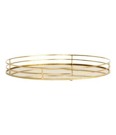 Guld. En rund bricka i metall med låg kant. Höjd 2,5 cm, diameter 25 cm.