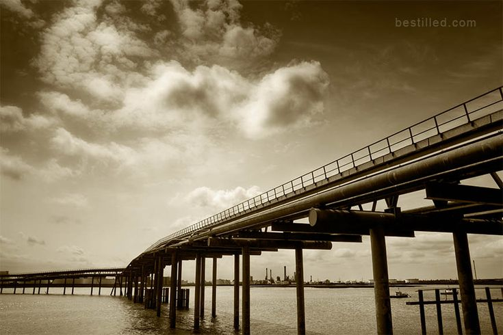 """""""Oil Bridge II"""" - atmospheric soft clouds over a disused pier with oil pipes above the river Thames at Canvey Island, Essex, England. Landscape art in sepia tone by Joseph Westrupp, bestilled.com. Click the image to buy a giclee print (options include frames, canvases, metal prints, and more)."""