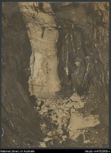 Lee, William Harrison, d. 1965. Man crouching down in a mine shaft, Long Tunnel Extended Mine, Walhalla, Victoria, 1906 [picture]