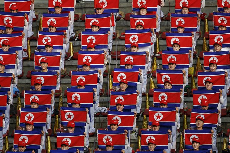 North Korean fans hold flags and sing the national anthem before their team's preliminary 2018 World Cup and 2019 AFC Asian Cup qualifying soccer match against Philippines at the Kim Il Sung Stadium in Pyongyang, North Korea