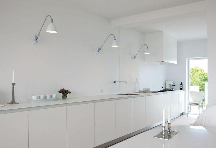 Det superenkle Bulthaup-køkken står knivskarpt langs væggen. Den horisontale effekt understreges af en række hvide Bestlite-lamper. Ekstra stole, stablet i køkkenet. Stakken af 7'er-stole udgør i sig selv en skulpturel installation.
