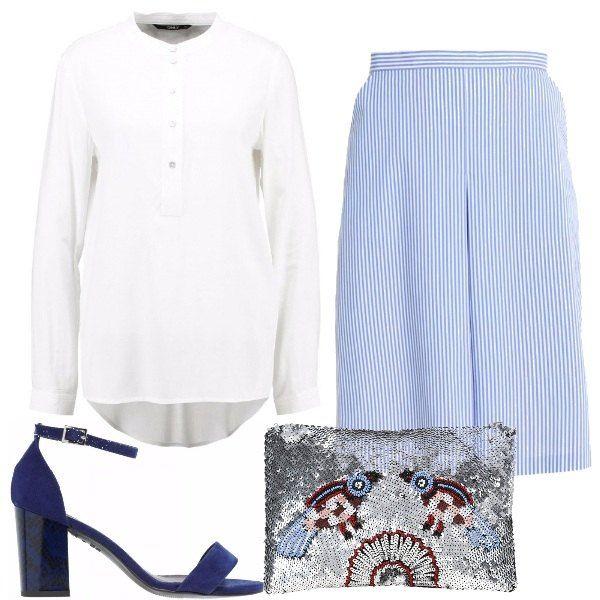 La gonna a righine azzurre, con la blusa bianca è perfetta, un forte tocco di colore è donato dai sandali blu dal tacco grosso e pitonato e dalla pochette con ricami