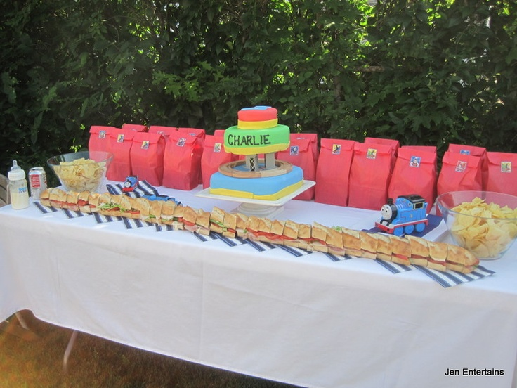 Thomas The Tank Engine birthday party theme. Gourmet baguette sandwiches for the grownups and pic nic dinner sacks for the kids. Thomas train motors along the fondant cake track.