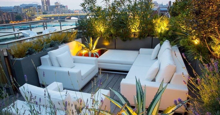 Calmly White Outdoor Living Furniture Surrounds With Green Plant And Warm Lighting In The Wooden Deck.