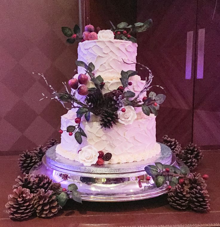 Perfect for a Christmas wedding, this soft-iced 3 tier cake is dressed with pine cones, berries and winter greenery. www.kellylou.com