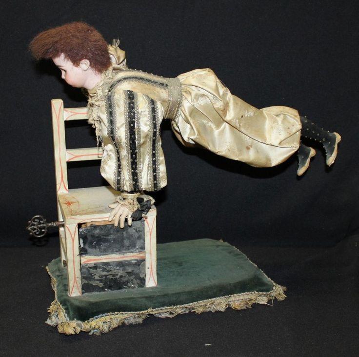 """""""Clown Acrobate sur sa chaise"""" automate à musique de fabrication française de la maison VICHY (circa 1900) avec tête allemande en biscuit coulé de la maison SIMON & HALBIG, bouche ouverte et yeux en verre, corps en carton moulé et mains en composition. Mécanisme à quatre mouvements. Musique à un air. Etat de marche. Habillage ancien. Plateau reposoir à quatre pieds. Clef d'origine. Haut : 43 cm Larg : 37 cm. Expert : François THEIMER. Le Chesnay Enchères - 13/02/2016"""