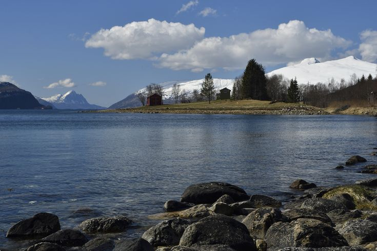 Seashore and mountains with snow in background against a blue sky, picture from the North of Norway.