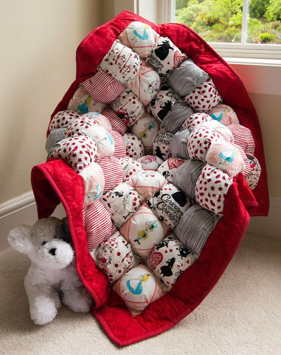 This Puff quilt/bubble blanket/biscuit quilt for babies measures ~ 37 x 37 with all cotton top featuring Alice in Wonderland characters including Alice of course, the Chesire Cat, the white rabbit, the Queen of Hearts and more! The quilt is framed by a wonderful red batik that sets off this lovely quilt. This quilt is just darling and will make a perfect shower gift or give your little boy/girl/grandchild many hours of fun!  Each square is like a little pillow and contains...