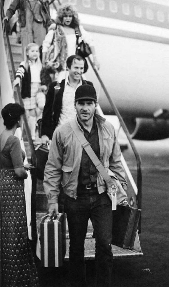 This behind the scene photo is from the movie Indiana Jones and the Temple of Doom (1984). The film was directed by Steven Spielberg and the cast includes Harrison Ford, Kate Capshaw, Amrish Puri, Roshan Seth, Philip Stone, Jonathan Ke Quan. This photo was taken when the actor Harrison Ford arriving in Sri Lanka for the filming of Indiana Jones and the Temple of Doom. Frank Marshall, Kate Capshaw and Jessica Capshaw also can be seen in this picture.