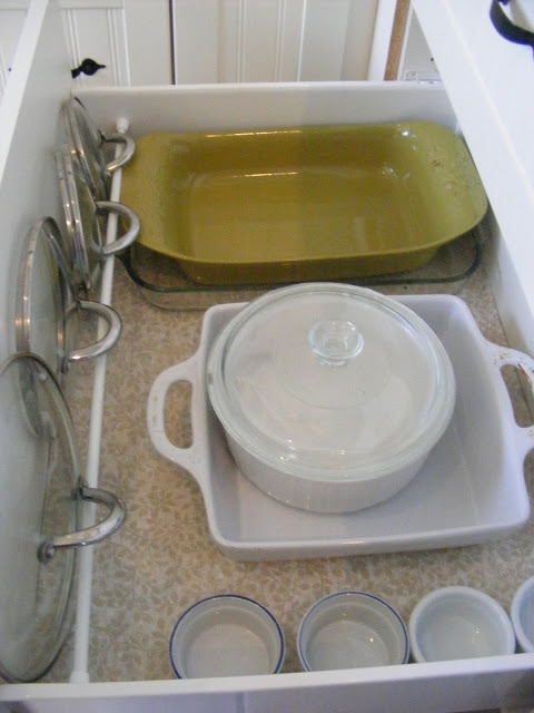 Clever idea - pot lids are held in place by a tension rod placed across the front of a drawer.....   The Complete Guide to Imperfect Homemaking: {OrganizedHome} Day 6: A Peek Inside My Kitchen