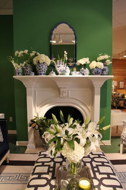 Another pinner says...Classic white fireplace offset by kelly green walls, competing patterns, and a collection of white flowers in blue chinoiserie vases and pots. By Wesley Hall at High Point Market 2012.