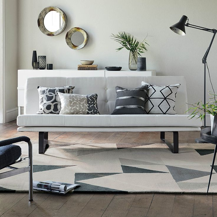 Scion Modul Rugs offer a stylish pop art design featuring charcoal and grey triangular shapes on a silver grey rug.