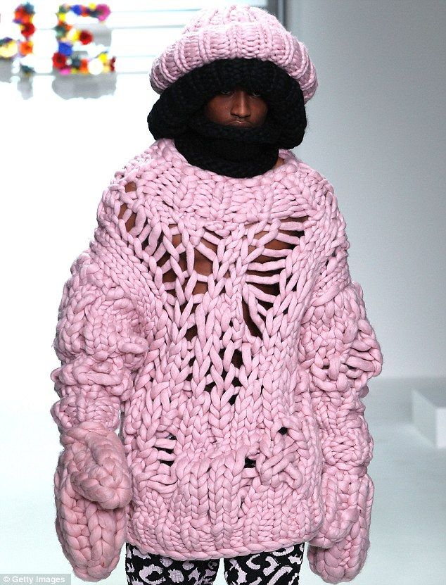 Ha! Knitwits on the catwalk! At least he won't catch a cold: A model wearing a large pink knitted jumper with match hat during the Sibling show at the London Collections